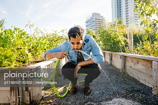 Young man drinking from hose in sunny, urban community garden - p1192m2130302 by Hero Images