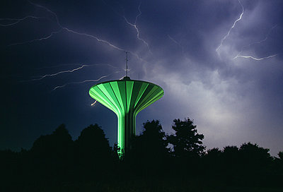 Thunderstorm against mushroom shaped water tower and silhouette trees - p1025m789167f by Torbjörn Arvidson
