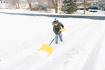 Little boy shoveling the icy driveway. - p1166m2152178 by Cavan Images