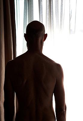 Glatzköpfiger Mann hinter Vorhang am Fenster - p1248m1138277 von miguel sobreira