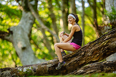 Smiling woman sitting on fallen tree log in forest - p300m2282419 by Mikel Taboada