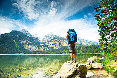 A backpacker stops at a lake to look at the mountains. - p343m1184704 by Rob Hammer