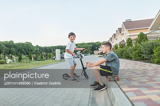 Boy sitting on skateboard while brother riding push scooter on cobbled street