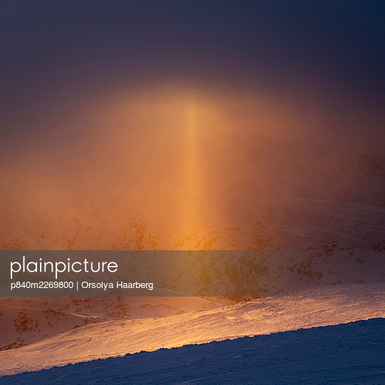 Sun pillar (optical phenomenon) that appears against the setting sun in light snow. Sognefjellet, Norway. April. - p840m2269800 by Orsolya Haarberg