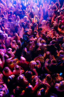 Looking down on a dance floor at a night-club as a Dj plays music, the crowd moves on a blur on the dance floor. - p1057m2164231 by Stephen Shepherd