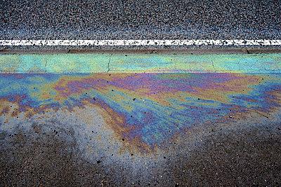 Ölfleck auf dem Asphalt einer Straße - p1057m2168560 von Stephen Shepherd