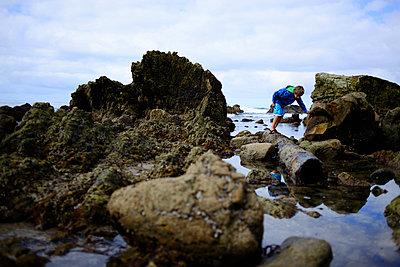 Boy searching something while standing on rocks at Laguna Beach - p1166m1542031 by Cavan Social