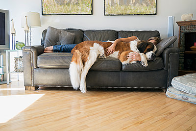 Woman and Saint Bernard dog laying on sofa - p1192m1078264f by Hero Images