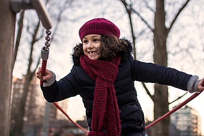Portrait of a happy little girl on a playground on a winter day - p300m1188592 by Marco Govel