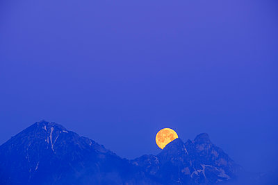 Germany, Bavaria, Moon hiding behind peaks of Tannheim Mountains at blue dawn - p300m2198890 by Martin Siepmann