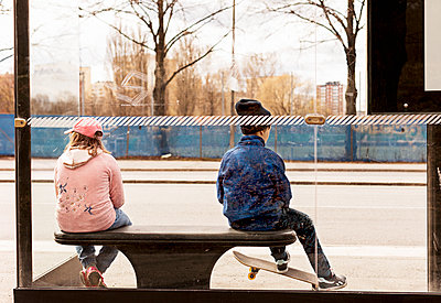 Boy and girl sitting on bus stop - p312m1495277 by Susanne Kronholm