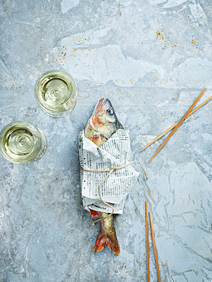 Wineglasses and raw fish wrapped in newspaper - p312m2102006 by Matilda Lindeblad