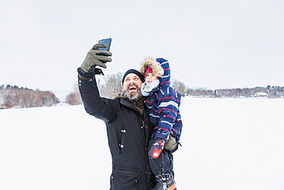 Father taking selfie with son in snow - p352m1536602 by Calle Artmark