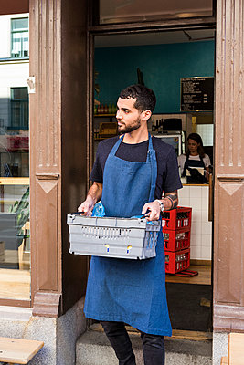 Young male owner carrying crate against restaurant - p426m2046531 by Maskot