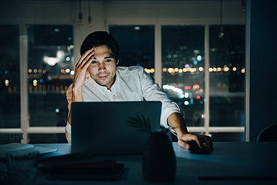 Businessman looking at laptop while working late in dark creative workplace - p426m2194825 by Maskot