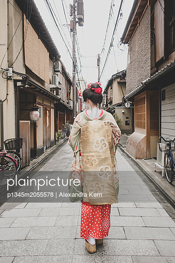 A woman dressed in the traditional geisha style wearing a kimono  - p1345m2055578 by Alexandra Kern