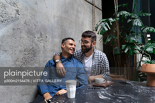 Gay couple relaxing together at outdoor cafe, Barcelona, Spain - p300m2154476 by VITTA GALLERY