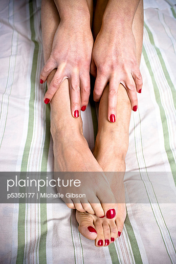 Close up of red nails on hands and feet - p5350177 by Michelle Gibson