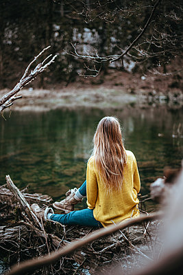 Woman sits next to a river - p1455m2081773 by Ingmar Wein