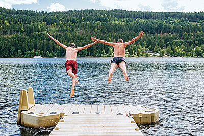 Germany, Lake Titisee, two men jumping into lake from a jetty - p300m1535151 by Kiko Jimenez