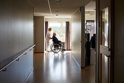 Full length side view of female nurse pushing senior man on wheelchair at hospital corridor - p426m1494018 by Maskot