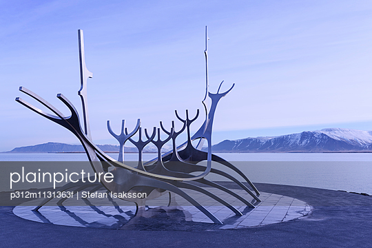 Modern sculpture with lake and mountains in background