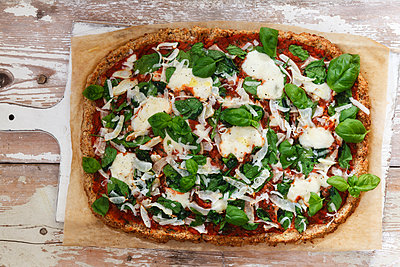 Glutenfree pizza with cauliflower bottom, tomatoes and spinach leaves - p300m1417267 by Eva Gruendemann