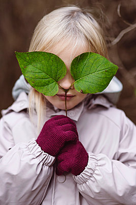 Portrait of blond little girl covering her eyes with green leaves - p300m2139757 by Ekaterina Yakunina