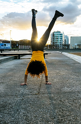 Young woman with afro hair doing handstand on street against sky during sunset - p300m2243142 by Marco Govel
