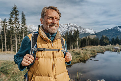 Smiling mature man with backpack standing against sky at Salzburger Land, Austria - p300m2266780 by Mareen Fischinger