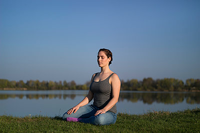 Young woman meditating on the lakefront - p552m1333266 by Leander Hopf