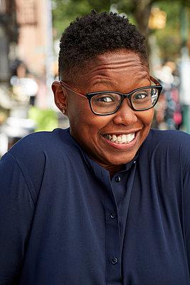 Portrait of Black woman shrugging on city sidewalk - p555m1231804 by Granger Wootz