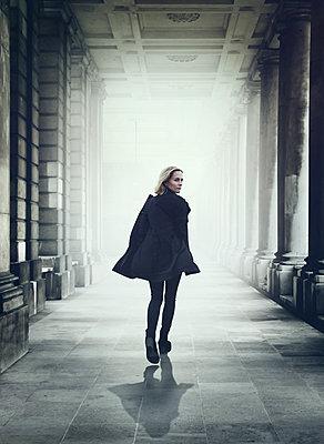 Frau in schwarzem Mantel - p984m2022594 von Mark Owen