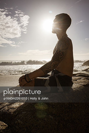 Man practises meditation on the beach at sunset - p1640m2261010 by Holly & John