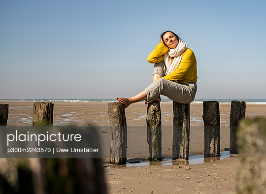 Woman with eyes closed sitting on wooden post at beach during sunny day - p300m2243579 by Uwe Umstätter