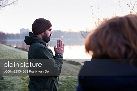 Mature man with hands clasped meditating at waterfront - p300m2293456 by Frank van Delft