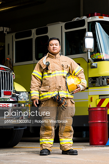 Serious Chinese fireman posing near fire trucks