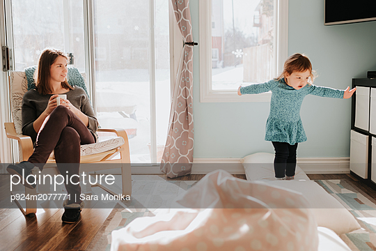 Mother watching toddler daughter jumping on cushions on living room floor - p924m2077771 by Sara Monika