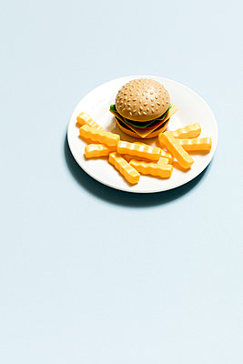 High angle view of burger and fries toys in plate on blue background - p1094m1467623 by Patrick Strattner