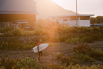Surfer carrying surfboard - p1108m2090449 by trubavin