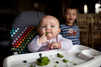 Baby girl eating food on high chair while brother standing in background - p1166m1416158 by Cavan Images