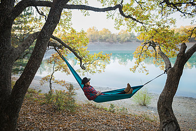 Italy, Man lying in hammock near lake - p1427m2174066 by Oleksii Karamanov