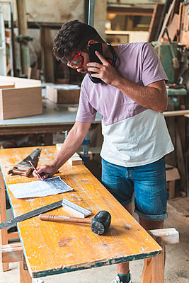 Male carpenter talking on smart phone while working in workshop - p300m2252572 by Josu Acosta