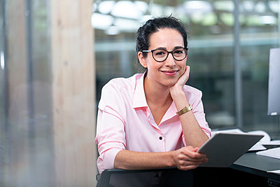 Smiling businesswoman with eyeglasses holding digital tablet at office - p300m2265183 by Florian Küttler