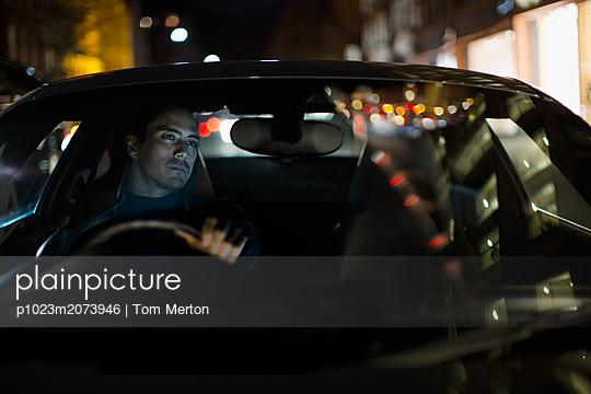 Man driving car at night - p1023m2073946 by Tom Merton