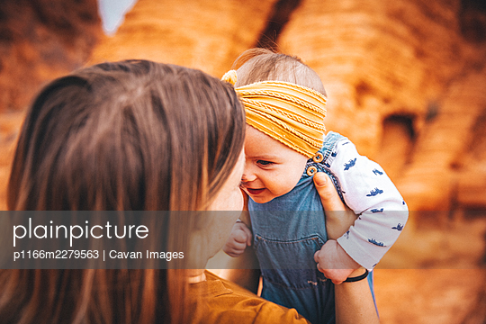 A young woman with a baby is standing near red rocks in Valley of Fire - p1166m2279563 by Cavan Images