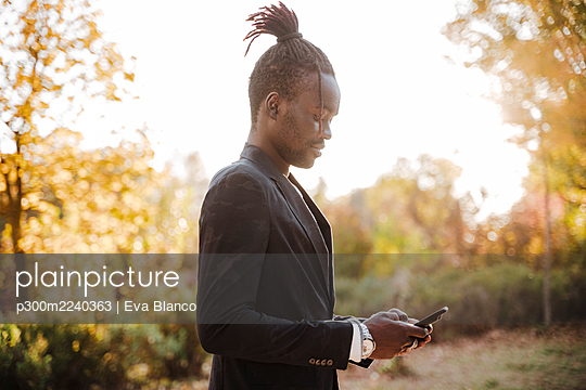Stylish man using smart phone in park - p300m2240363 by Eva Blanco