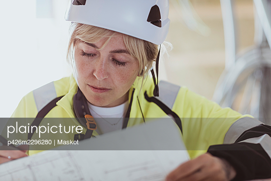 Female builder analyzing floor plan while working at construction site - p426m2296280 by Maskot