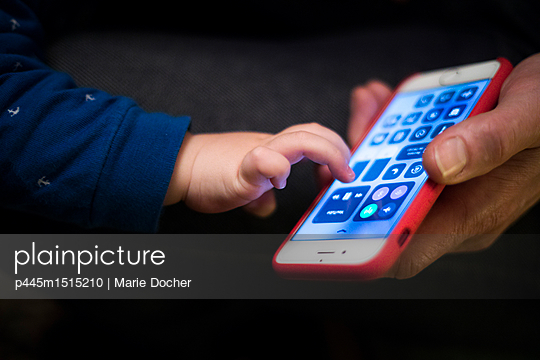 Baby playing with mobile phone - p445m1515210 by Marie Docher