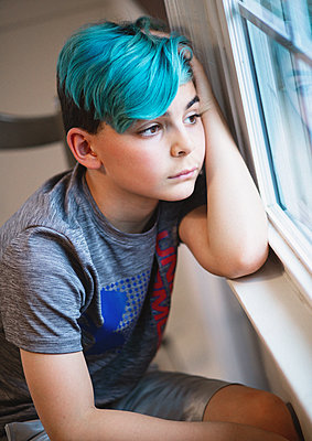 Boy with blue hair looks out of window - p1211m2193448 by Danny Weiss